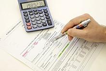 Heizkosten: Abrechnung, Taschenrechner und Stift in der Hand