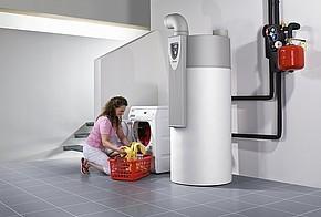 Frau befüllt Waschmaschine neben einer Warmwasser-Wärmepumpe.
