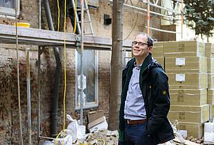 Heizspiegel-Botschafter Till Eichmann vor einem Gebäude, dessen Fassade gedämmt und saniert wird.